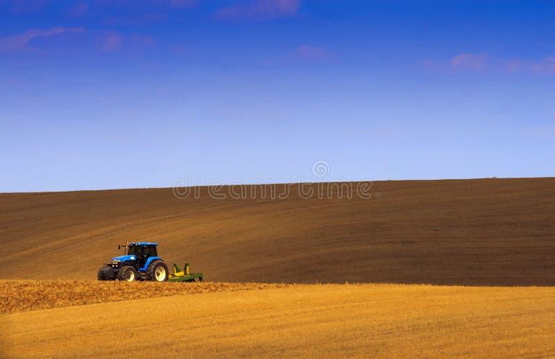 Het land van de tractor onder de schaduw van hemelblauw. royalty-vrije stock foto's