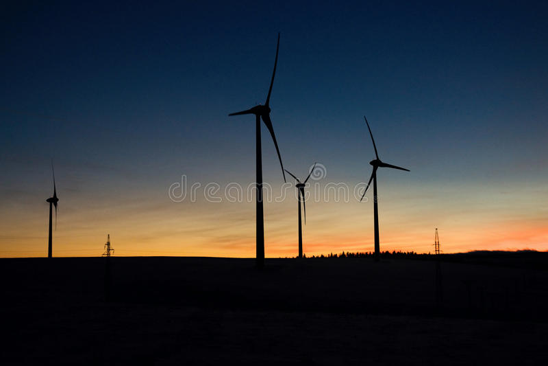 Het landbouwbedrijf van de windturbine bij zonsondergang stock foto's