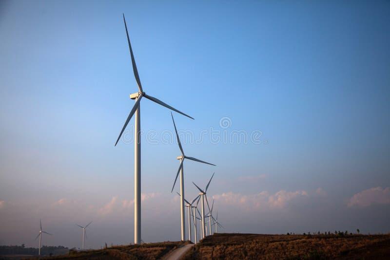 Het landbouwbedrijf van de windturbine van silhouet bij zonsondergang stock foto