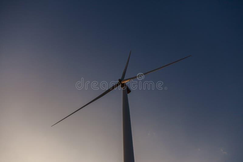 Het landbouwbedrijf van de windturbine van silhouet bij zonsondergang stock foto's