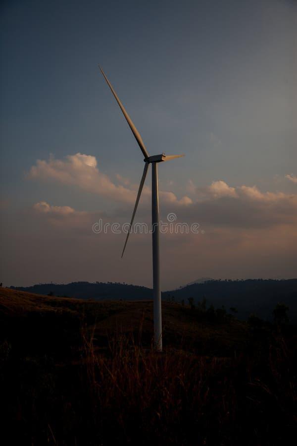 Het landbouwbedrijf van de windturbine van silhouet bij zonsondergang stock afbeeldingen
