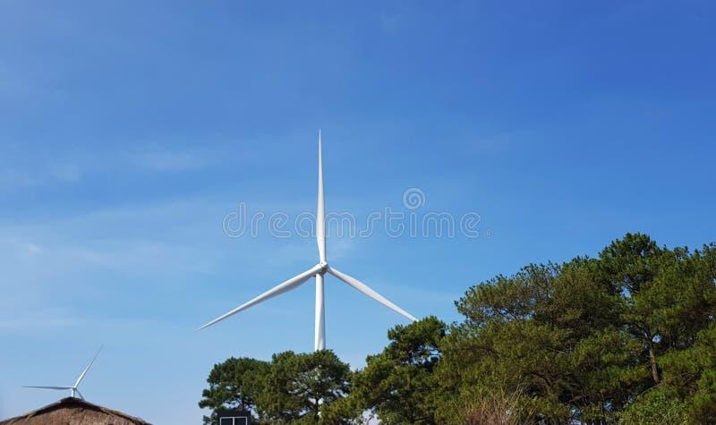 Het landbouwbedrijf van de windturbine tijdens mooie zonsondergang Alternatieve groene ener stock foto's