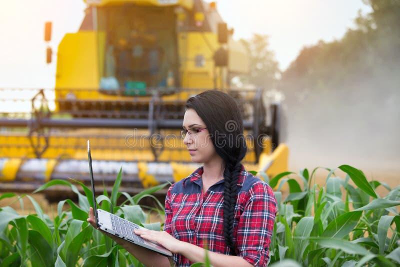 Het landbouwersmeisje op gebied met maaidorser royalty-vrije stock fotografie