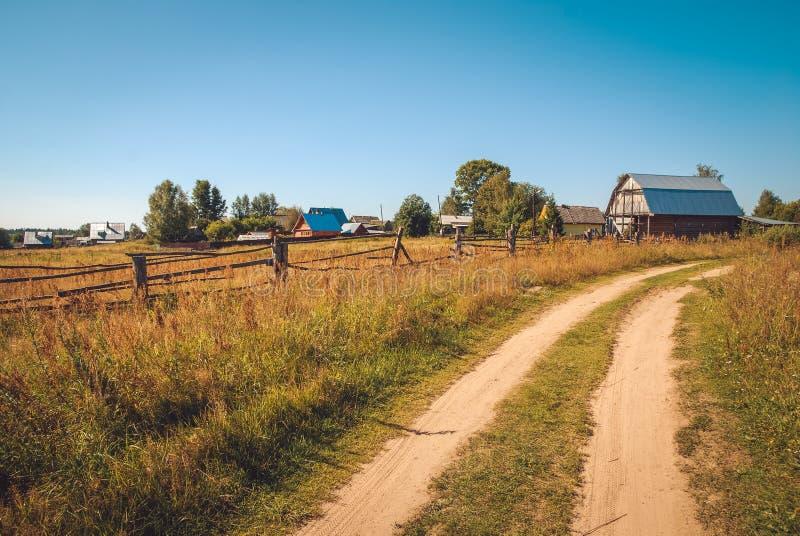 Het landelijke die weg uitrekken zich in de afstand door de gebieden op de dorpsachtergrond met bomen en huizen door helder worde stock foto