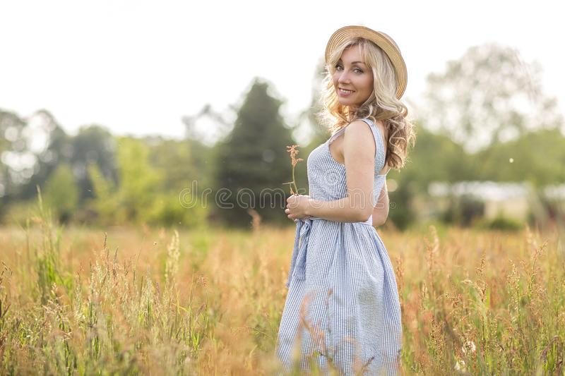 Het landelijke, landelijke leven Het lopen door de jonge vrouw van het weideblonde in een hoed zomer royalty-vrije stock foto's