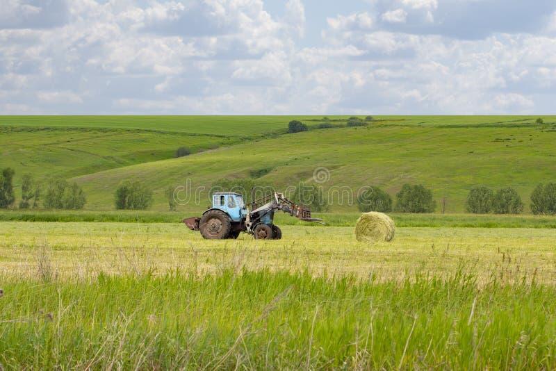 Het landelijke leven, verzamelt een landelijke tractor een schoof van hooi op een groene weide Rond hooibroodje, voedsel voor hui royalty-vrije stock fotografie