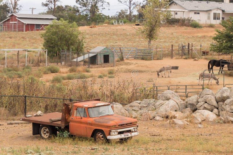Het landelijke oude landschap van het tijd uitstekende gebied van een oude oranje flatbed vrachtwagen, westelijke landbouwbedrijf royalty-vrije stock afbeeldingen