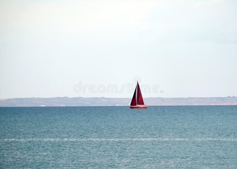 Het landschap met jacht met hoge rode zeilen drijft in het overzees in kalm water stock afbeelding