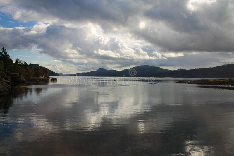 Het landschap met nog wateren & de zeilboot in afstand en de grote, expansieve hemel met gezwollen Cumuluswolken dachten in het w stock afbeelding