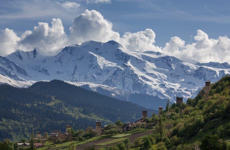 Het landschap, met Svan-watchtowers en landbouwgebieden op de achtergrond van snow-capped berg bereikt en wolken, Svaneti een hoo royalty-vrije stock afbeeldingen