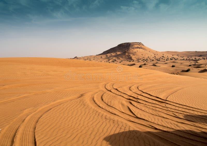 Het Landschap van de Emiratiwoestijn met Berg op Achtergrond en Gebogen band-Sporen in Voorgrond royalty-vrije stock afbeeldingen