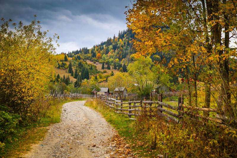 Het landschap van het de herfstlandschap met kleurrijke bos, houten omheining en landelijke weg in Prisaca Dornei royalty-vrije stock fotografie