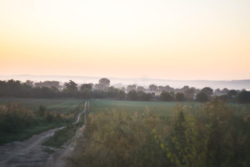 Het landschap van de ochtend Zonsopgang achter het dorp op het gebied stock afbeeldingen
