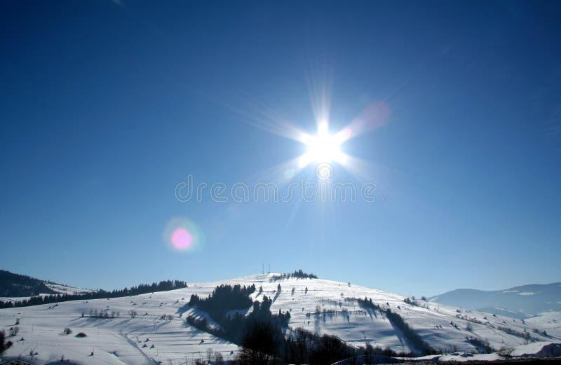 Het landschap van de winter Behandeld door sneeuwheuvels en de zon van de stervorm op blauwe hemel stock foto