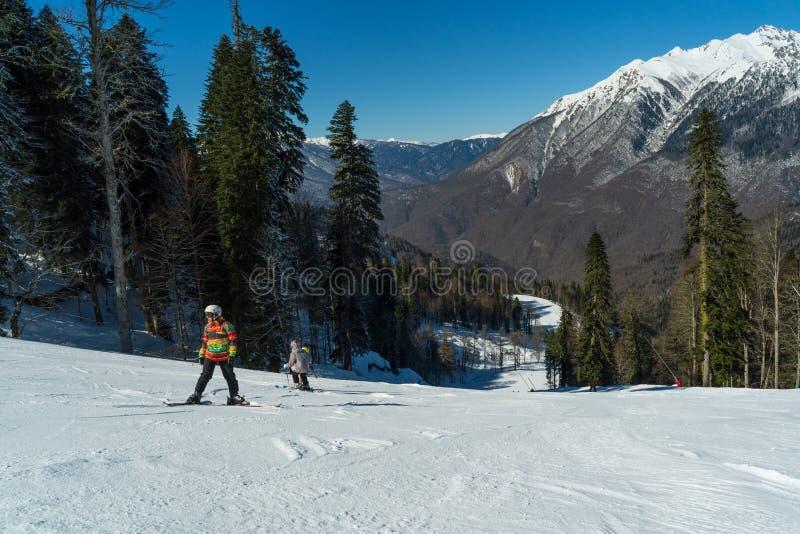 Het landschap van de winter Skiërs en snowboarders die op hellingen van de skitoevlucht van Krasnaya Polyana berijden stock afbeelding