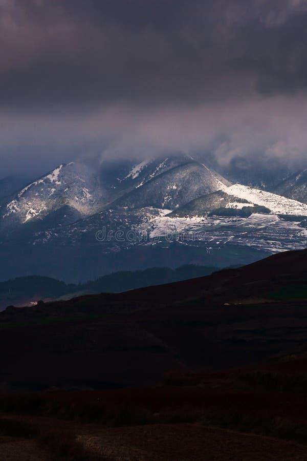 Het landschap van de winterbergen met dramatische onweerswolken, licht in het donkere glanzen op de sneeuwberg Yunnan, Zuid-China stock afbeeldingen