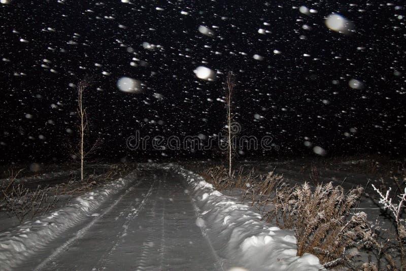 Het landschap van de de winternacht met weg op een gebied in de sneeuw De sneeuwval, blizzard en de donkere hemel stock foto's