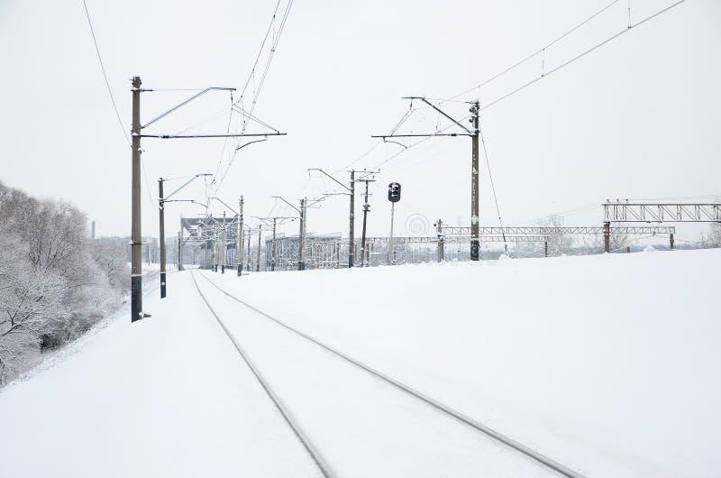 Het landschap van de de winterspoorweg, Spoorwegsporen in het snow-covered industrieland stock fotografie