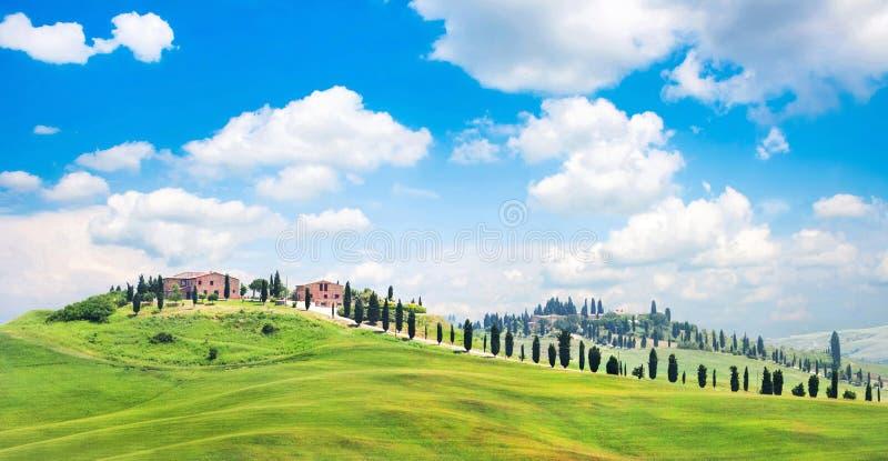 Het landschap van Toscanië met huizen op een heuvel stock afbeelding