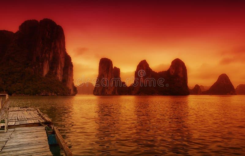 Het landschap van Vietnam van de Halongbaai onder een oranje zonsondergang