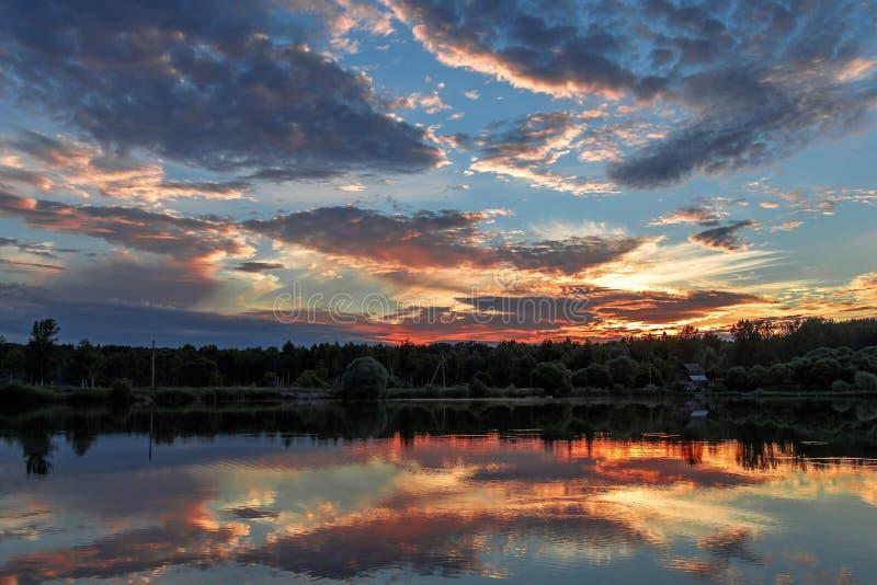 Het landschap, zonsondergang over de meerwolken wordt weerspiegeld in het water stock foto