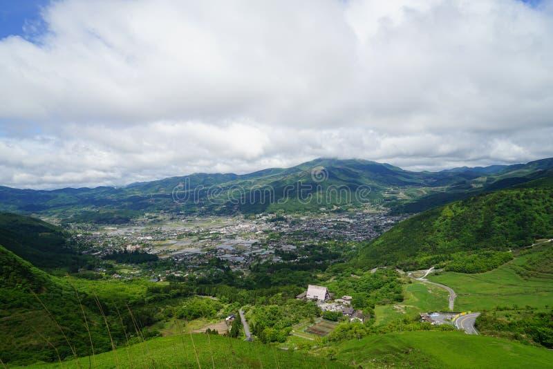 Het landschapspanorama van de groenberg en stadsmening met witte bewolkte hemel stock afbeelding