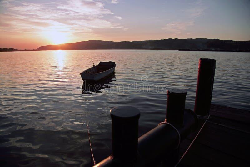 Het landschapswater van de landschapszonsondergang en dok en boot stock fotografie