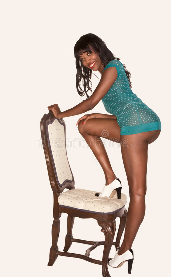 Het langbenige zwarte meisje in sensueel stelt groen dragen stock afbeeldingen