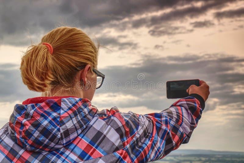 Het lange haar leuke meisje neemt beeld door smartphone stock afbeeldingen