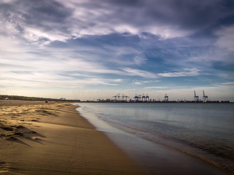Het lange lege schone strand van zandstogi in Gdansk, Polen met de scheepswerf van Stalin met kranen op de achtergrond stock foto