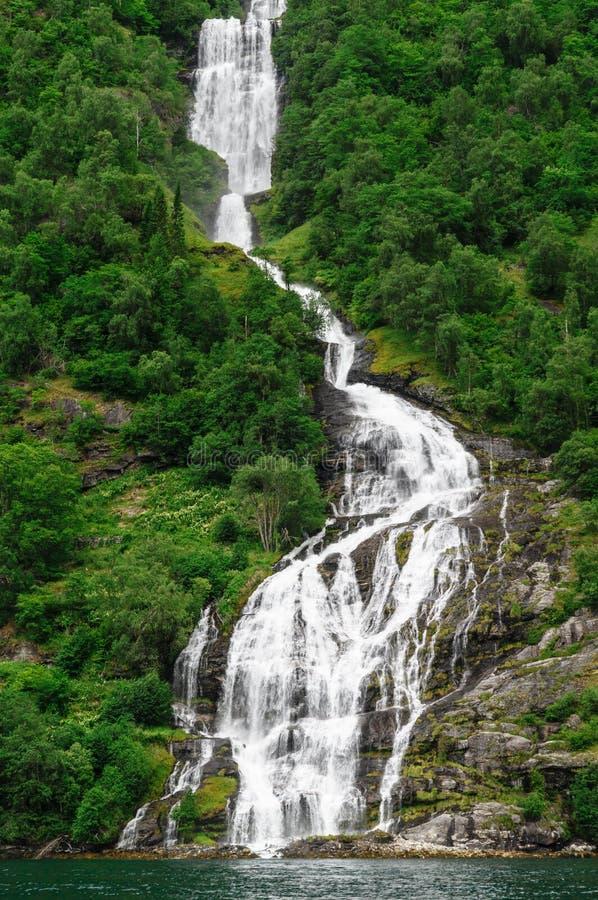 Het lange Noorse waterval inflowing in Geiranger-fjord stock foto