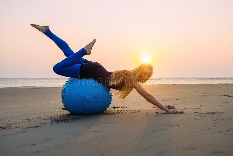 Het langharige blonde is bezig geweest met Pilates op een opleidingsbal op het strand tijdens zonsondergang Geschikte vrouw die h royalty-vrije stock foto's
