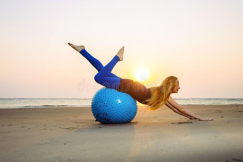 Het langharige blonde is bezig geweest met Pilates op een opleidingsbal op het strand tijdens zonsondergang Geschikte vrouw die h stock afbeelding