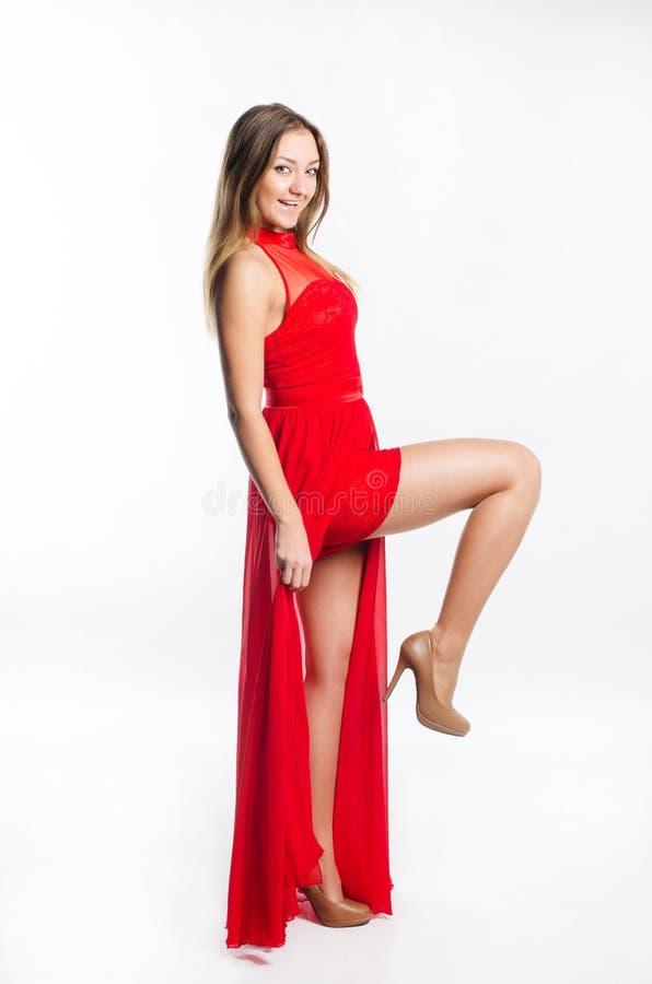 Het langharige blonde in een rode kleding toont de benen stock afbeelding