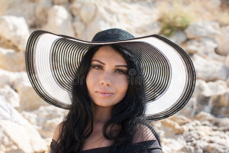Het langharige donkerbruine stellen in hoed tegen witte rots royalty-vrije stock afbeelding