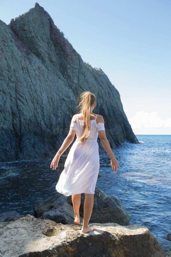 Het langharige meisje in witte kleding stelt tegen donkere klip royalty-vrije stock afbeeldingen