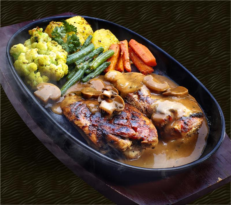 Het lapje vlees is behandeld in de saus van de paddestoelbarbecue, die op warmhoudplaat wordt gediend met groenten en aardappels, royalty-vrije stock foto