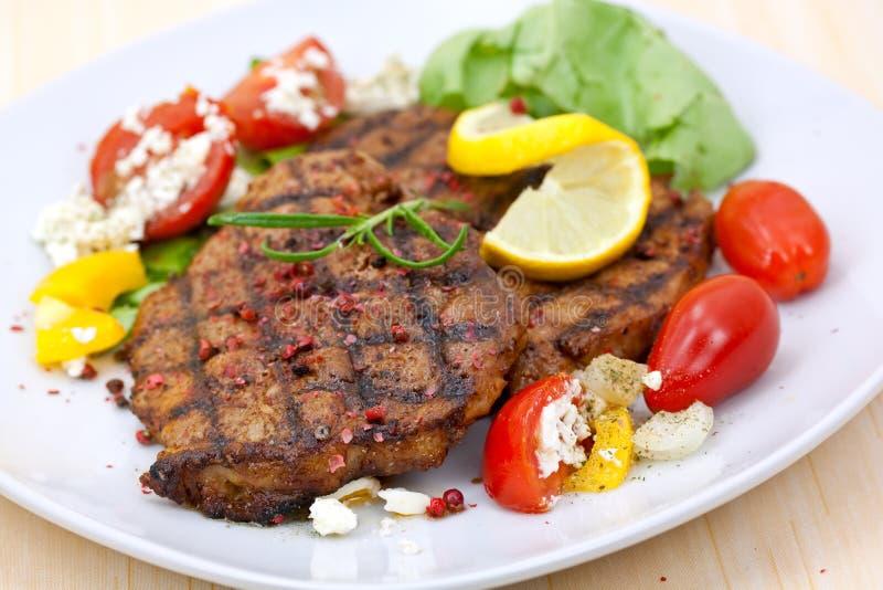 Het lapje vlees van het varkensvlees, dat met salade wordt geroosterd stock afbeelding