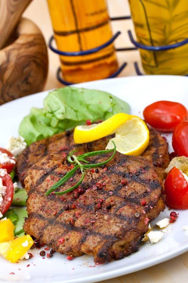 Het lapje vlees van het varkensvlees, dat met salade wordt geroosterd stock afbeeldingen
