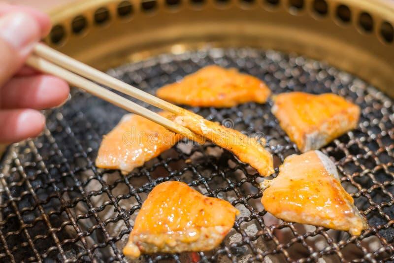 Het lapje vlees van zalmvissen het koken over houtskoolgrill stock afbeelding