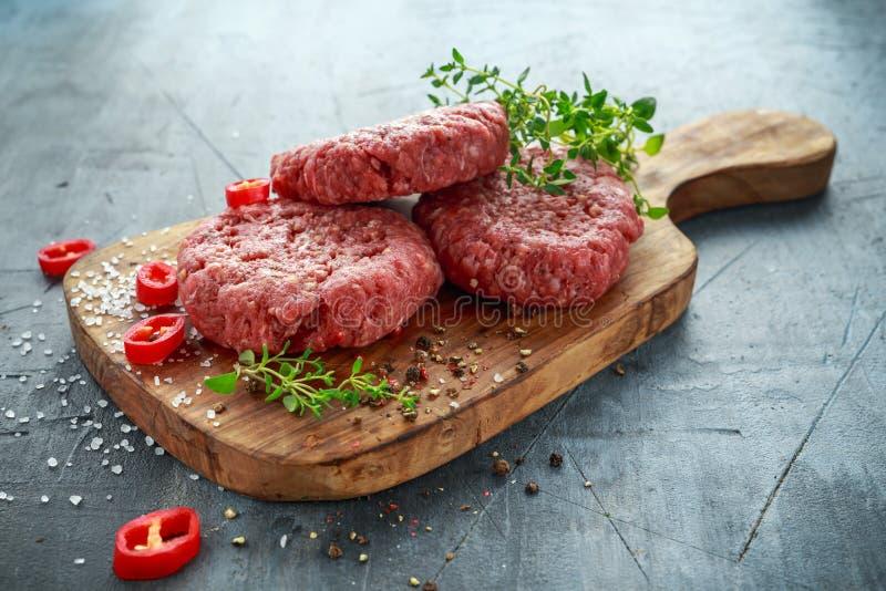 Het lapje vleesburgers van het huis Met de hand gemaakte Ruwe Fijngehakte Rundvlees op houten raad royalty-vrije stock foto's