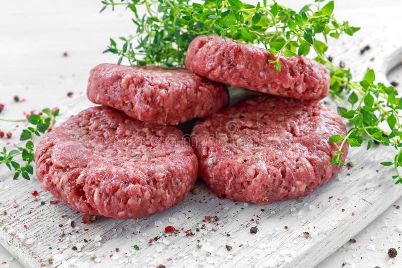 Het lapje vleesburgers van het huis Met de hand gemaakte Ruwe Fijngehakte Rundvlees op houten raad stock foto
