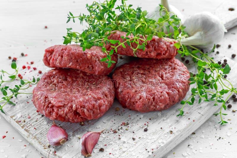 Het lapje vleesburgers van het huis Met de hand gemaakte Ruwe Fijngehakte Rundvlees op houten raad stock fotografie