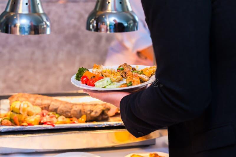 Het lapje vleesvarkensvlees, tomaat, groente is in de schotel Een schotel van de mensengreep in het restaurant stock foto