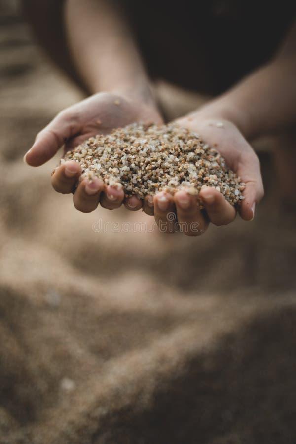Het laten vallen van zand van beide handen van vrouw stock foto