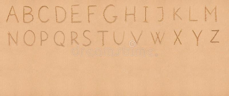 Het Latijnse alfabet van het handschrift op zand met royalty-vrije stock afbeeldingen