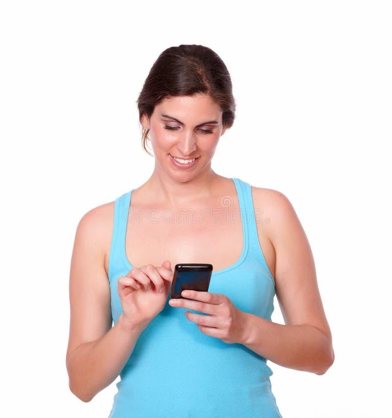 Het Latijnse sportieve vrouw texting op cellphone stock foto