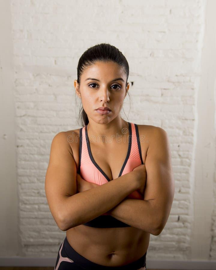 Het Latijnse sportvrouw stellen in woest en badass ziet uitdrukking met geschikt slank lichaam onder ogen stock foto's
