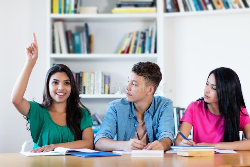 Het Latijnse vrouwelijke student opheffen dient klaslokaal in stock afbeeldingen