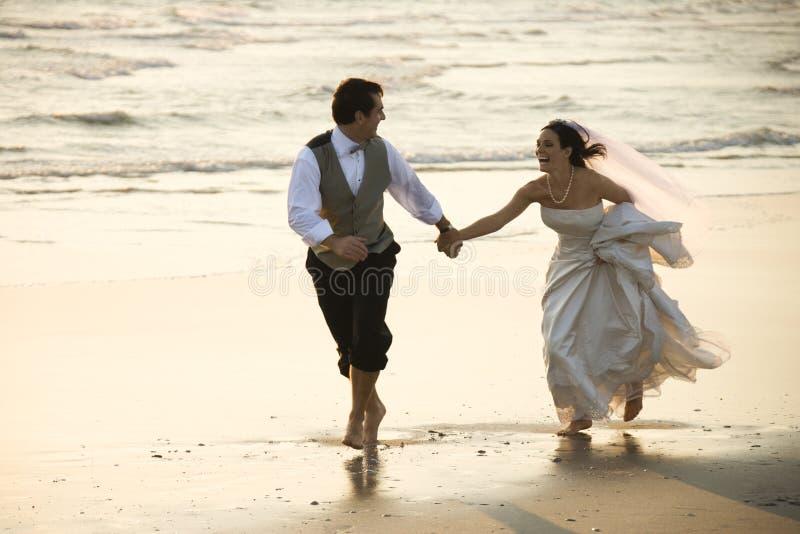 Het leeglopende strand van het paar.